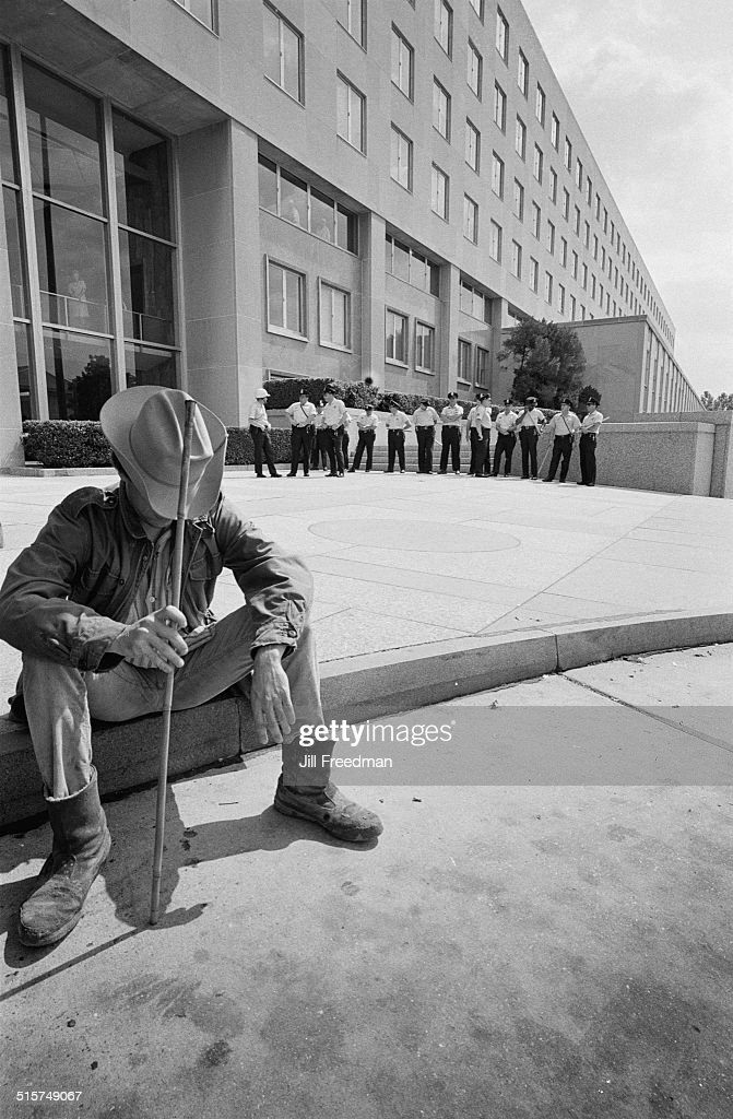 A man resting outside a well-guarded government building in Washington, DC, during the Poor People's Campaign, 1968.