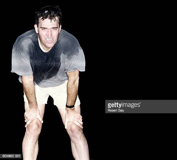 man resting with hands on knees, wearing sweat-soaked t-shirt - inclinar se pose imagens e fotografias de stock