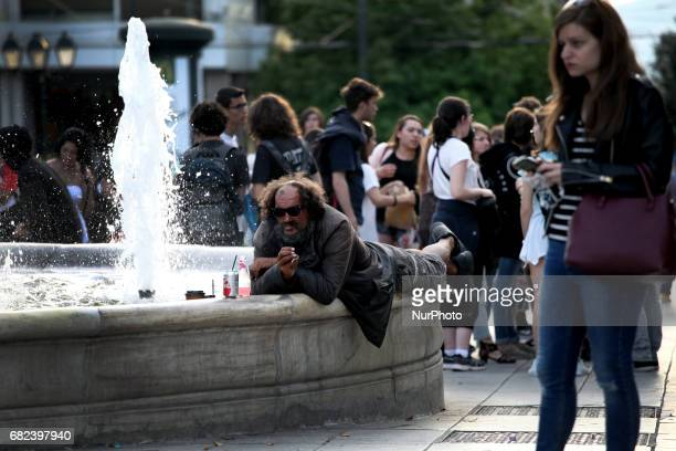 A man rests by the water fountain in Syntagma square in Athens Greece May 11 2017