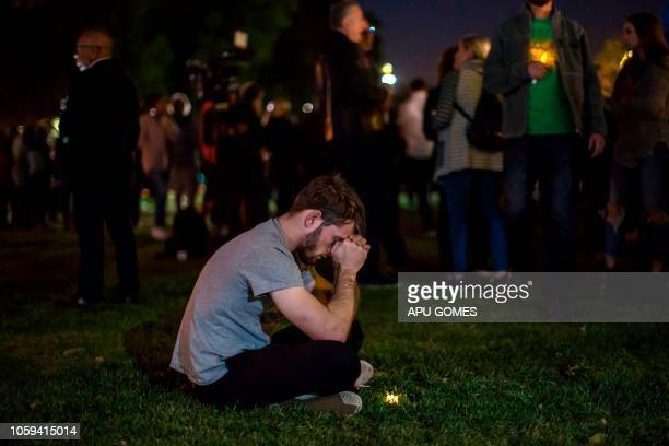 Man rests his head on his hands during a vigil to pay tribute to the victims of a shooting in Thousand Oaks, California, on November 8, 2018. - A...
