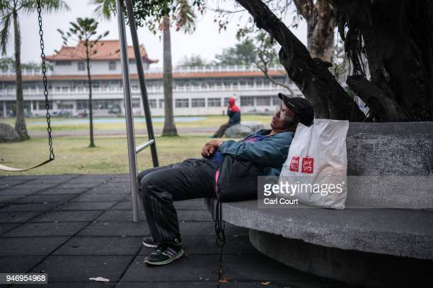 A man rests in a school sports field near Xingang Fengtian Temple that has been allocated for pilgrims who are following the statue of Mazu on day...