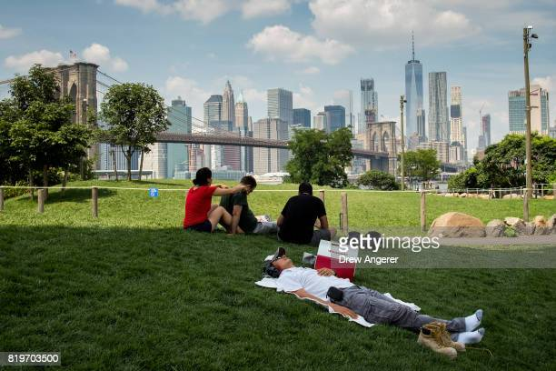 A man rests in the shade in Brooklyn Bridge Park July 20 2017 in the Brooklyn borough of New York City Thursday is forecasted to be the hottest day...