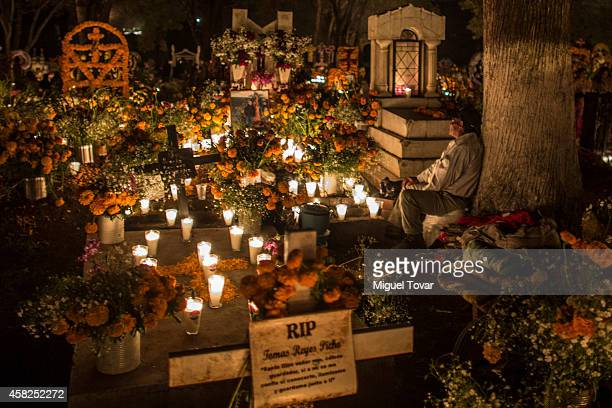 A man rests next to a grave during the celebration of the Day of the Dead in which people remember those relatives and friends that have passed away...