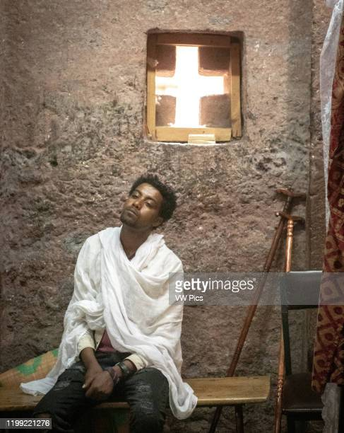 Man rests on a bench inside the rock hewn monolithic church of Bet Maryam in Lalibela , Ethiopia.