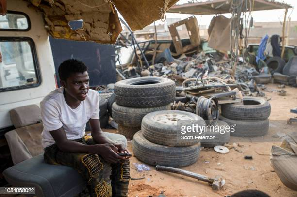 Man rests on a car seat at a yard where cars are broken down for scrap, as Nigeriens struggle to cope with the challenges of daily life in the...