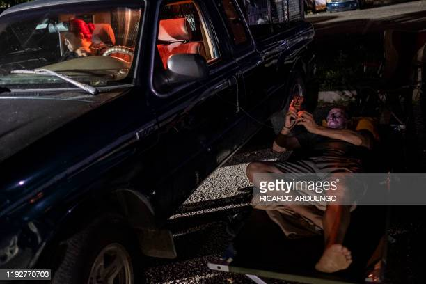 TOPSHOT A man rests on a cot next to his car in a parking lot in Guanica Puerto Rico on January 9 after a powerful earthquake hit the island Puerto...