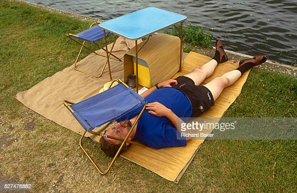 A man rests on a stretch of grass his face shielded from a bright sky beneath a camping stool during a particularly hot afternoon at the Henley Royal...