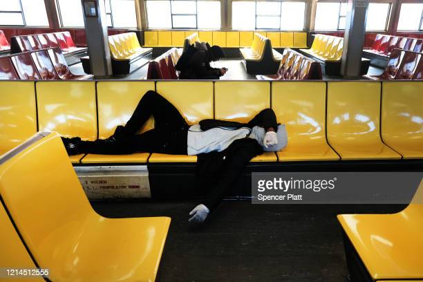 A man rests on an empty Staten Island Ferry on March 24 2020 in New York City Across the country schools businesses and places of work have either...
