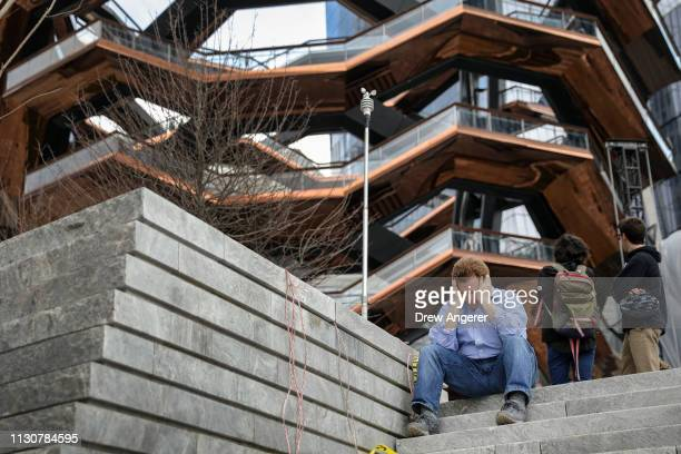 A man rests on the entrance steps during the grand opening of phase one of the Hudson Yards development on the West Side of Midtown Manhattan March...
