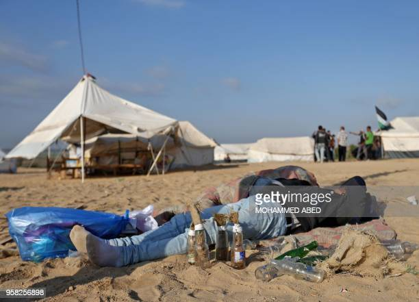 TOPSHOT A man rests on the sand next to bottles to be used as molotov cocktails as Palestinians prepare to demonstrate along the border with the Gaza...