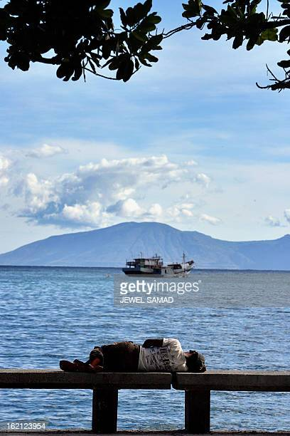 A man rests on the shore as a fishing boat is seen anchored in Dili 27 June 2007 East Timor's nearly 530000 voters are to cast ballots to elect 65...