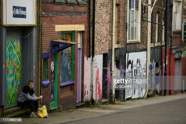 A man rests outside a closed phone shop adjacent to street art in the city centre of StokeonTrent northern England on October 1 2019 Brexit is giving...
