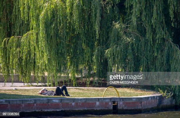 A man rests under a weeping willow tree on the banks of the Spree River in Berlin as temperatures are to rise until 32 degrees celsius in the German...