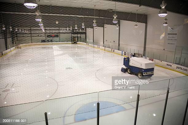 Man resurfacing ice at indoor hockey arena