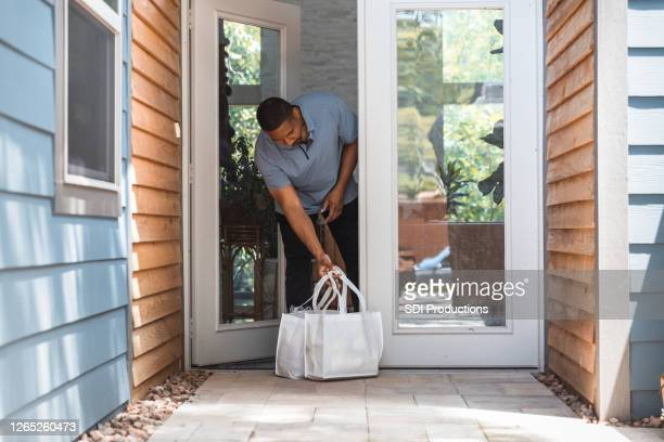 man retrieves groceries from front porch after contactless delivery - picking up stock pictures, royalty-free photos & images