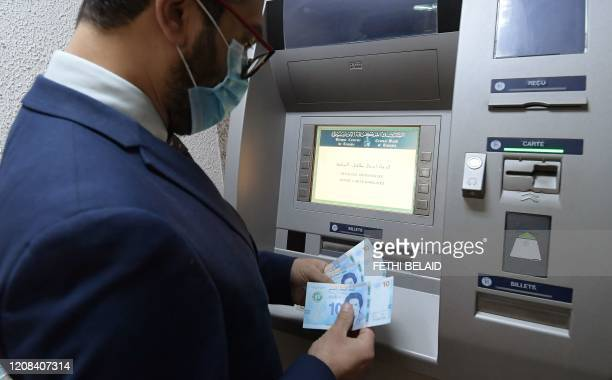 Man retrieves newly circulating Tunisian bank notes from an ATM in the capital Tunis, on March 27, 2020. - The Central Bank of Tunisia today put new...