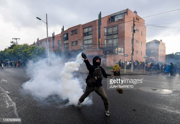 Man returns a tear gas canister at police during a demostration outside Colombian President Ivan Duque's house in Bogota on May 1, 2021. - Thousands...