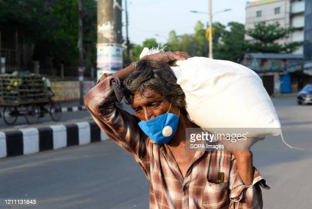 Man returns back home after receiving relief supplies. During the Coronavirus crisis besides the government, many organisations are donating relief...