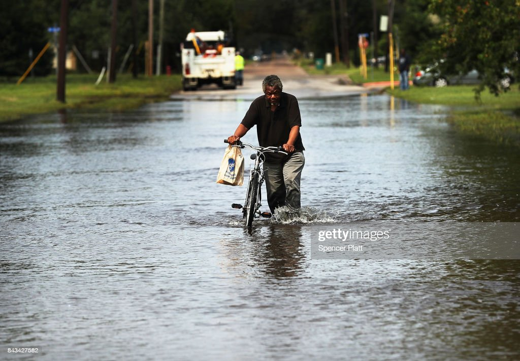 A man returns from the grocery store through high water along a street in Orange as Texas slowly moves toward recovery from the devastation of Hurricane Harvey on September 6, 2017 in Orange, Texas. Almost a week after Hurricane Harvey ravaged parts of the state, some neighborhoods still remained flooded and without electricity. While downtown Houston is returning to business, thousands continue to live in shelters, hotels and other accommodations as they contemplate their future.