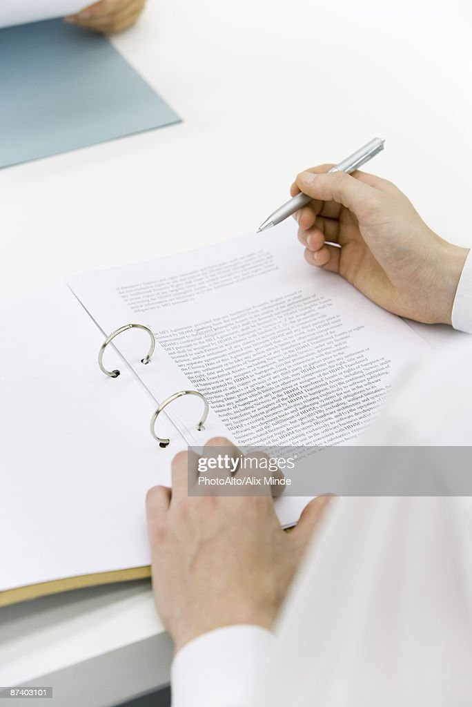Man reviewing document in binder, over the shoulder view, cropped : Stock Photo
