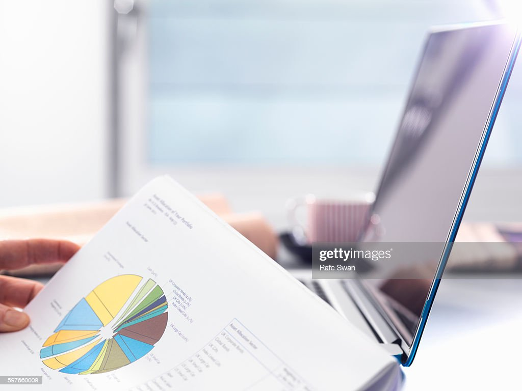 Man reviewing financial affairs using investment statement and laptop : Stock Photo