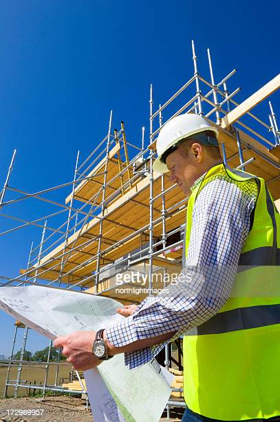 Man reviews building plans on site