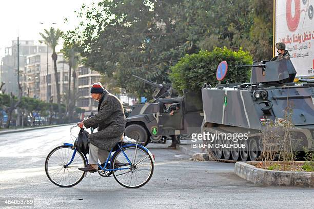 A man ride his bicycle past Lebanese soldiers standing guard in the street at the northern entrance of the northern port city of Tripoli on January...