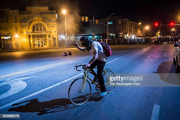 A man ride his bike as officers fire tear gas an d pepper balls as protestors walk for Freddie Gray on West North Avenue and protest around the city...