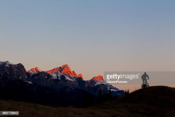 A man rides a a singletrack trail at sunrise in the Rocky Mountains of Alberta, Canada.