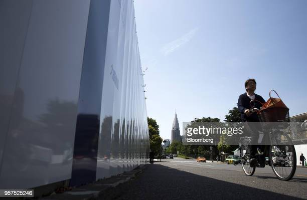 A man rides a bicycle along a fence of the construction site of the New National Stadium a venue for 2020 Summer Olympics and Paralympics in Tokyo...