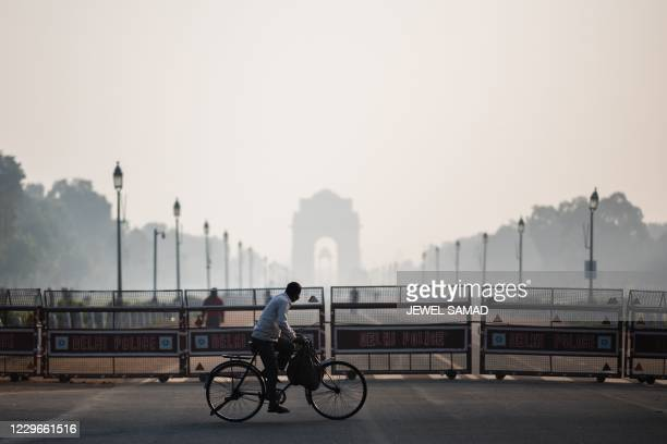 Man rides a bicycle along a street amid smoggy conditions in New Delhi on November 18, 2020.
