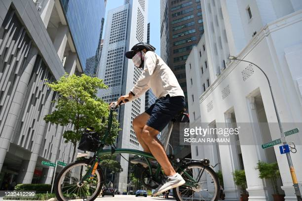 Man rides a bicycle along a street at the Raffles Place financial business district in Singapore on April 20, 2021.