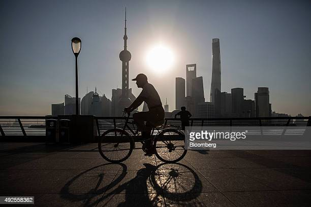 A man rides a bicycle along the Bund while buildings of Pudong's Lujiazui financial district stand across the Huangpu River as the sun rises in...