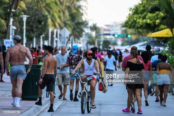 Man rides a bicycle as people walk on Ocean Drive in Miami Beach, Florida on June 26, 2020. - They are itching for a good time after months of...