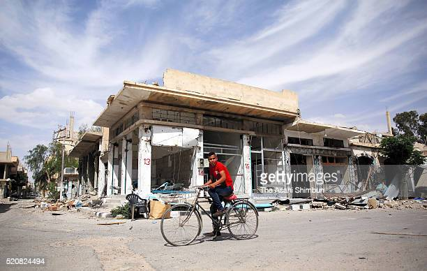 A man rides a bicycle at the destroyed Palmyra city on April 11 2016 in Palmyra Syria Russia backed Syrian troops recaptured the historic city on...