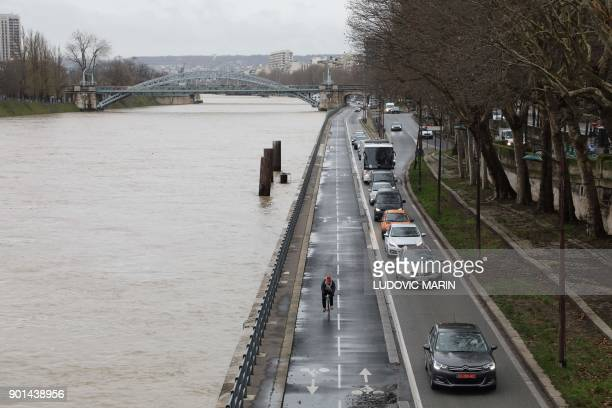 A man rides a bicycle close to car traffic along the river Seine in Paris which level has risen on January 5 2018 following heavy rains PHOTO /...