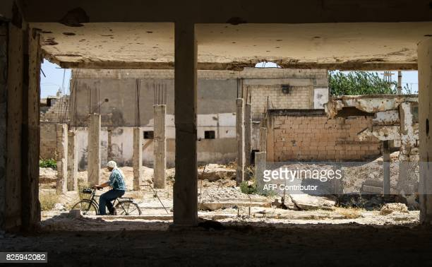 A man rides a bicycle down a street past a damaged building in the central Syrian rebelheld town of Talbiseh north of Homs on August 3 2017 A...