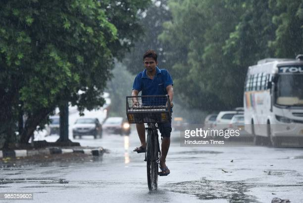 A man rides a bicycle during the premonsoon showers near Sheikh Sarai on June 27 2018 in New Delhi India The monsoon rains are expected to arrive on...