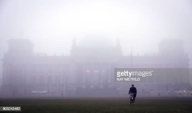 A man rides a bicycle in front of the fog covered Reichstag building that houses the lower house of Parliament 'Bundestag' in Berlin on January 10...