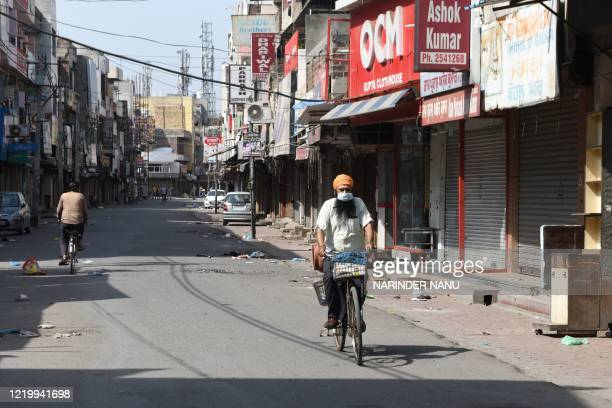Man rides a bicycle near closed shops after strict lockdown norms for weekends and public holidays were imposed as a preventive measure against the...