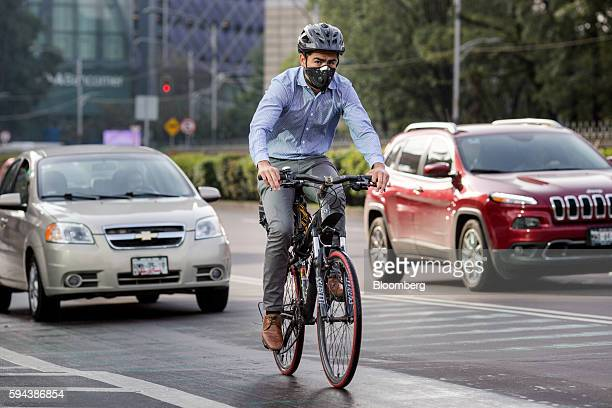 A man rides a bicycle next to traffic along the Paseo de la Reforma in Mexico City Mexico on Wednesday Aug 10 2016 Mexico's push to reduce air...