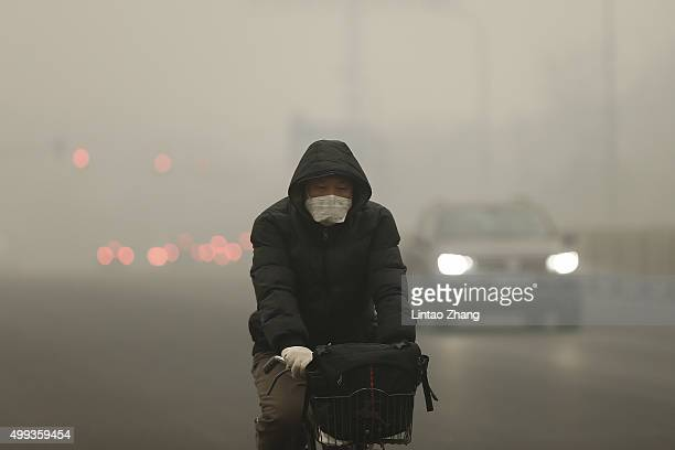 A man rides a bicycle on a day of heavy pollution on December 1 2015 in Beijing China China's capital and many cities in the northern part of the...