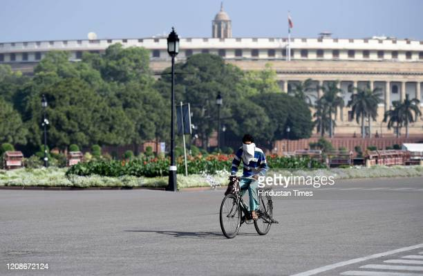 Man rides a bicycle on a deserted Rajpath during day 6 of the 21-day nationwide lockdown imposed by PM Narendra Modi to curb the spread of...