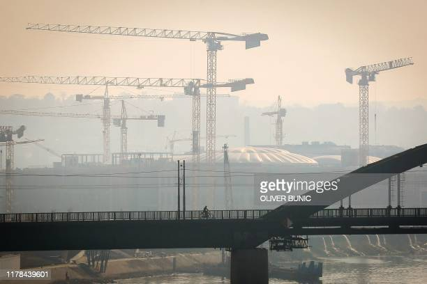 """Man rides a bicycle on one of Belgrade's bridges on October 27, 2019. - Serbian health authorities warned on October 27 against """"very high"""" air..."""