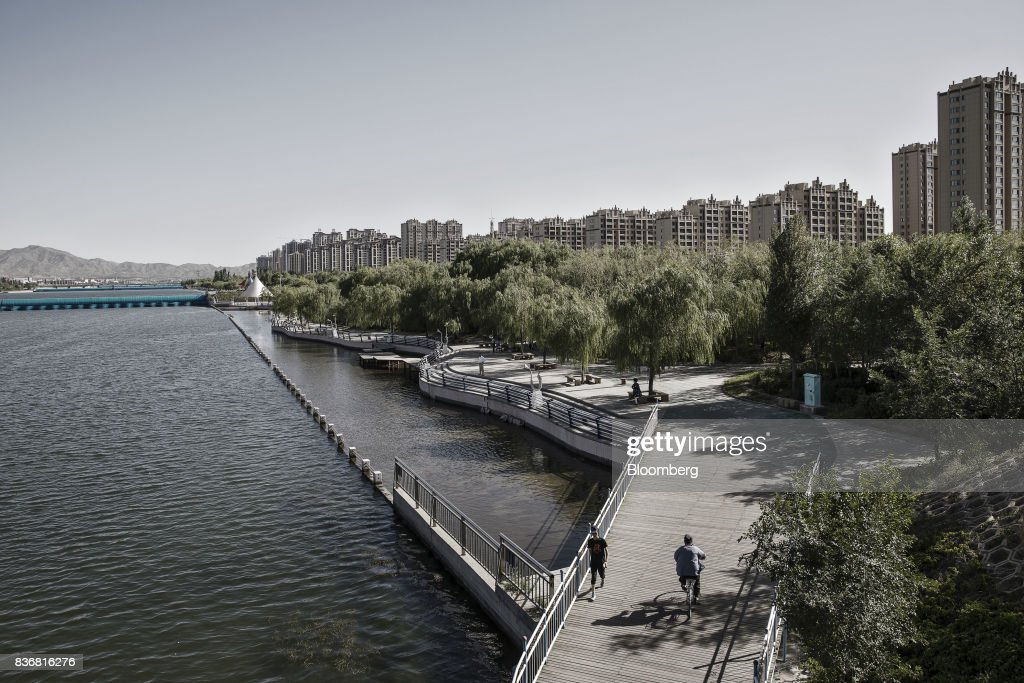 A man rides a bicycle over a bridge as new residential buildings stand in the distance in Baotou, Inner Mongolia, China, on Friday, Aug. 11, 2017. China's economy showed further signs of entering a second-half slowdown, as curbs on property, excess borrowing and industrial overcapacity began to bite. Photographer: Qilai Shen/Bloomberg via Getty Images