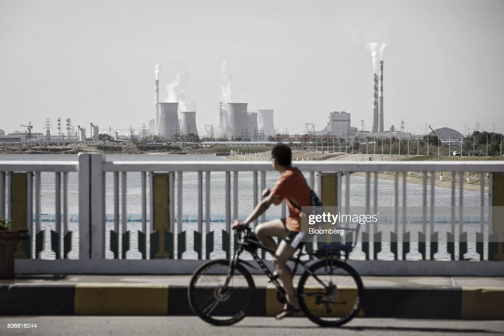 A man rides a bicycle over a bridge as power plants stand in the distance in Baotou, Inner Mongolia, China, on Friday, Aug. 11, 2017. China's economy showed further signs of entering a second-half slowdown, as curbs on property, excess borrowing and industrial overcapacity began to bite. Photographer: Qilai Shen/Bloomberg via Getty Images