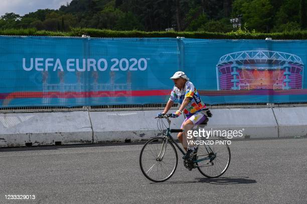 Man rides a bicycle past a banner of the Euro 2020 European football tournament on June 08, 2021 by the Olympic stadium in Rome, three days before...