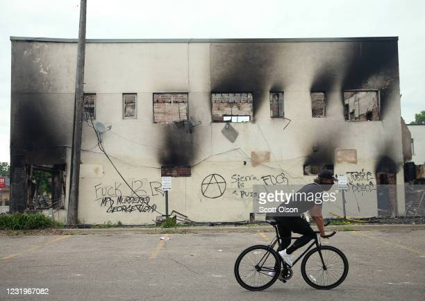 A man rides a bicycle past a burned out building after a night of protests and violence on May 29 2020 in Minneapolis Minnesota The National Guard...