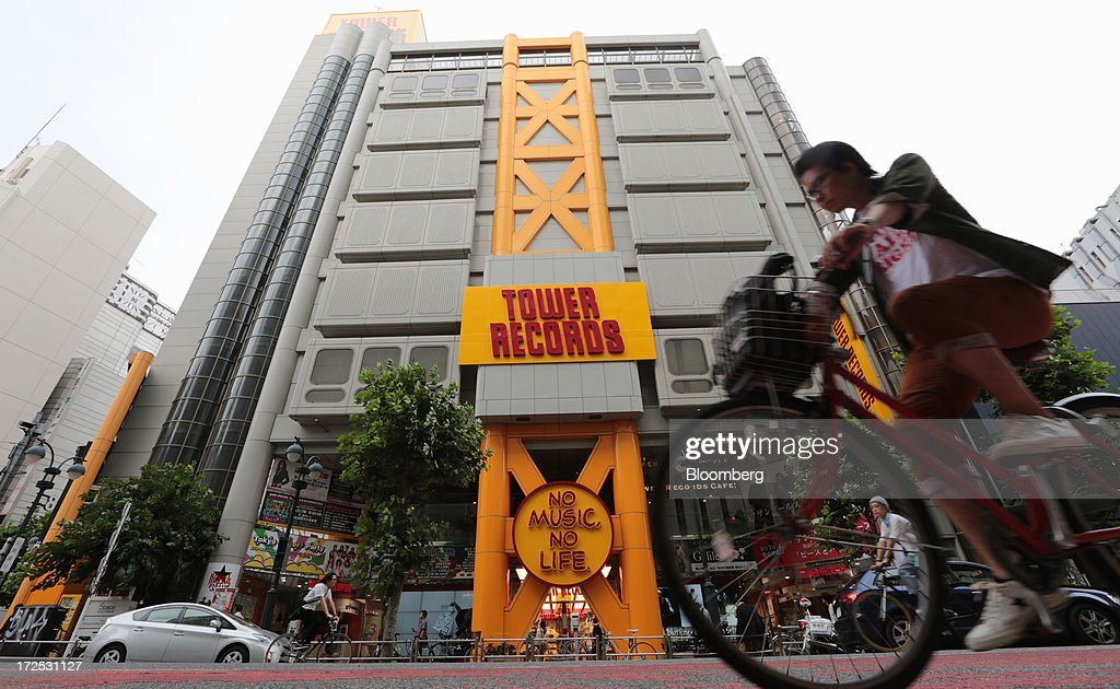 A man rides a bicycle past a Tower Records Japan Inc. store in Tokyo, Japan, on Monday, July 1, 2013. Music sales in the country rose for the first time in five years, led by tunes delivered on CDs and other physical media, bucking the trend in developed markets as cheaper downloads gain ground. Physical media made up 82 percent of Japanese music sales last year, versus 37 percent in the U.S., said the Recording Industry Association of Japan. Photographer: Yuriko Nakao/Bloomberg via Getty Images