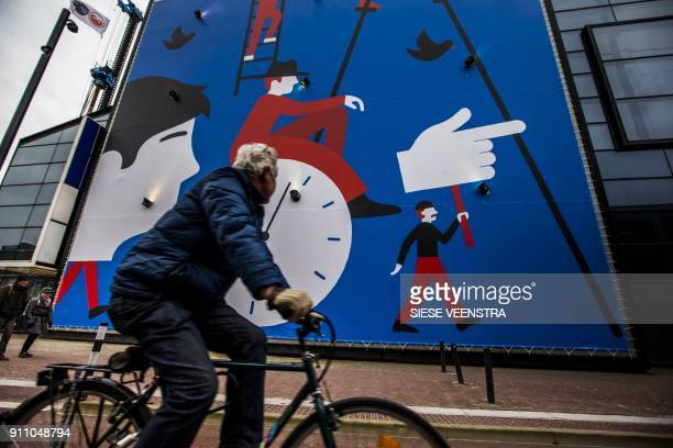 A man rides a bicycle past a wall painting with the logo of Leeuwarden Fryslan 2018 during the opening weekend of Leeuwarden the European Capital of...